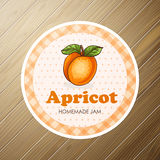 Round label, apricot jam on a wooden background Royalty Free Stock Images