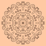 Round lacy brown pattern on beige background Stock Photos