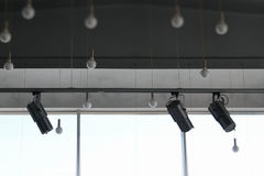 Round lamps on wires and track spotlights on rail system at studio. Studio lighting. Roof lamps and track spotlights on rail system stock photos