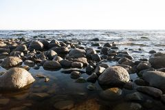 Round large stones on the beach, lake stock images