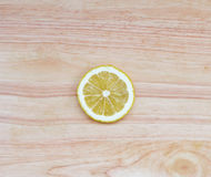 A round lemon slice on wooden table Stock Photography