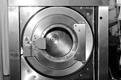Round loading hatch of the industrial washing machine. Black and white toning image Stock Photo