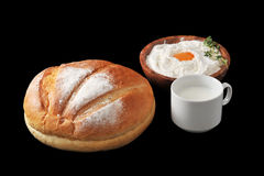 Round loaf of bread, milk in a Cup and the flour. With raw egg on wooden plate with rosemary on black background Stock Photo