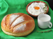 Round loaf of bread, milk in a Cup and the flour. With raw egg on wooden plate with rosemary on green background Stock Images