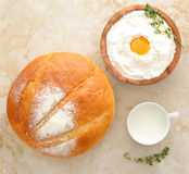Round loaf of bread, milk in a Cup and the flour. With raw egg on wooden plate with rosemary on marble background. top view Stock Photo