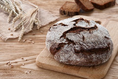 Round loaf of bread on a wooden background. A round loaf of bread with a knife and some barley ears a wooden background Royalty Free Stock Image