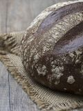 Round loaf of freshly backed sourdough bread on wooden backgroun royalty free stock photography