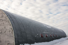 Round Long House in Snow. Round Long House in Under Cloudy Sky in Snowy Location stock photo