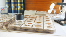 Round magnifying glass on album with coins from different countries Royalty Free Stock Image