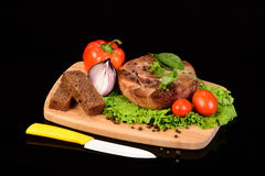 Round meat steak on a wooden board with vegetables Royalty Free Stock Photo