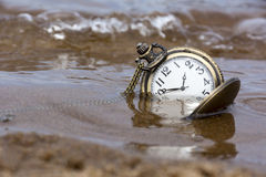 Round mechanical pocket watch on the sand under the water Stock Photos