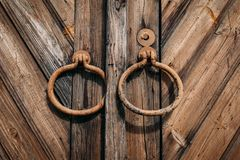 Round metal handles on closed old antique wooden gate or door. Close up stock images