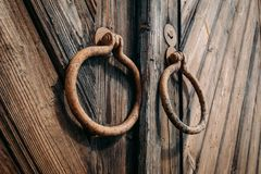 Round metal handles on closed old antique wooden gate or door. Close up royalty free stock photos