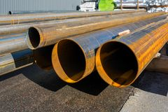 Round metal pipes on asphalt, close-up of a cut,. Round metal rolled metal tubes, close-up of a cut stock image