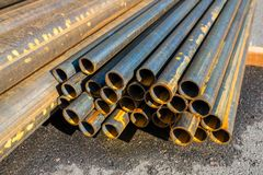 Round metal pipes on asphalt, close-up. Of a cut royalty free stock photos