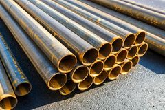 Round metal rolled metal tubes, close-up of a cut,. Round metal pipes on asphalt, close-up of a cut royalty free stock images