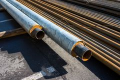 Round metal-rolling pipes. Round metal rolling tubes folded horizontally on the street royalty free stock photography