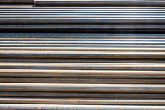 Round metal-rolling pipes. Round metal rolling tubes folded horizontally on the street stock photos
