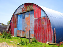 Round Metal Shed with Mismatched Paint. Round Metal Shed on Farm with Mismatched Paint on front surface Stock Photo