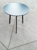 Round metal table on concrete floor. Modern design royalty free stock images