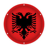 Round metallic flag of Albania with screw holes. Round metallic flag of Albania with six screw holes in front of a white background Royalty Free Stock Image