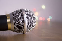 Round microphone silver and gold. Top of a microphone on gray background with bright colors royalty free stock images