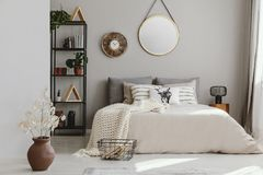 Round mirror and clock above bed with pillows in bright bedroom interior with flowers. Real photo royalty free stock photos