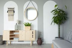 Round mirror hanging on the wall in real photo of grey living room interior with retro cupboard with lamp and books and fresh. Plant in the corner stock photo