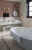 The round mirror and tub in the bathroom at home Stock Images