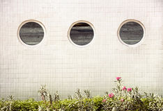 3 round mirror windows in a row on a white tiled building Royalty Free Stock Photo