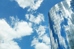 Round mirrored glass of modern office center building.Clear blue sky and reflection in windows stock photos