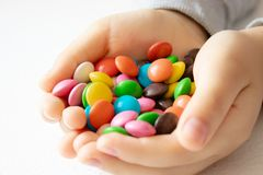 Round, multi-colored, chocolates. A pile of multi-colored candies. A child holds a candy stock image