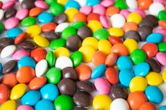 Round, multi-colored, chocolates. A pile of multicolored candies stock photos