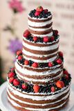 Round multi tiered wedding cake with sponge, cream, jam and berries on a circular base. Fresh blueberries and stock images