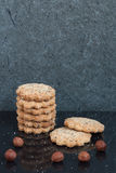 Round nut buttery cookies. A vertical stack of round nut buttery cookies are laid on a black background with some hazelnuts, sugar drops and a reflection with a royalty free stock image