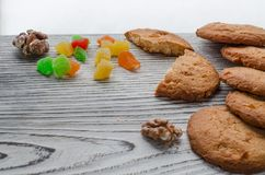 Round orange biscuits with colorful candied fruits and a slice of juicy orange lying on a wooden table against the background of stock photos