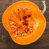 Round orange pumpkin half in cut. Close-up of fresh squash cutaway, ready for preparing. Seasonal fruit, healthy eating, nutrition concept Royalty Free Stock Image