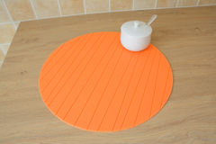 Round orange tablemat and sugar bowl on table Royalty Free Stock Photo