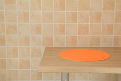 Round orange tablemat on table Stock Image