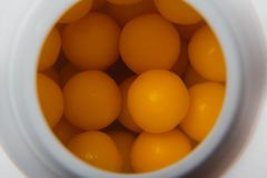 round orange vitamin close up inside a white bottle, medical concept, top view, close-up royalty free stock photos