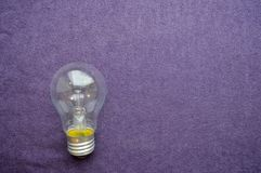 A round, ordinary, non-economical incandescent bulb. With a transparent socle background of purple cloth Stock Photos