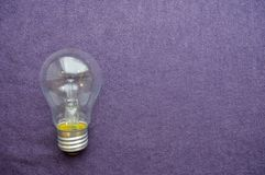 A round, ordinary, non-economical incandescent bulb with a transparent socle. Background of purple cloth Stock Photography