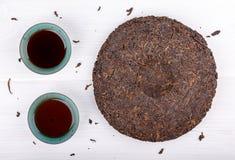 Round płaski dysk puer herbata i dwa filiżanki na bielu fotografia stock