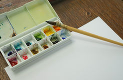 Round paint brush and watercolor palette put on drawing paper, F Stock Photography