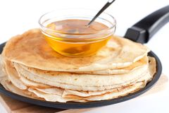 Round pancakes in a frying pan and honey Royalty Free Stock Image