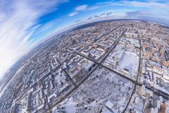 Round panorama aerial view on a winter city under a blue sky with white clouds: rows of streets with high-rise buildings and roofs stock photo