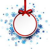 Round paper christmas ball on blue snowflakes. Stock Photos