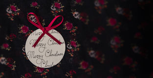 Round paper Christmas ornament with a red bow on floral fabric Stock Photos