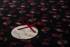Round paper Christmas ornament with a red bow on floral fabric Stock Images