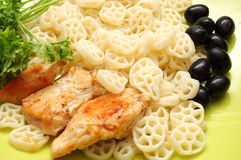 Round pasta with fried checken, parsley and olives Royalty Free Stock Image